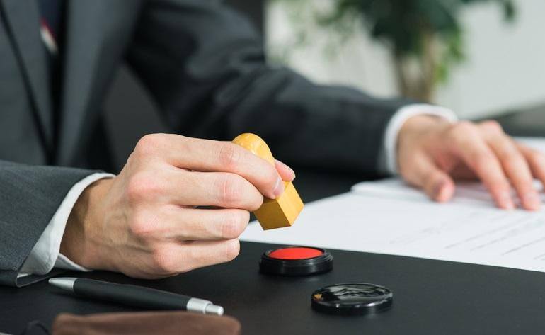 書類に捺印する男性